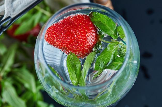 暗い表面に果物全体が入ったジュースのグラス