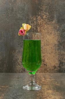 大理石の背景にジューシーな緑のレモネードとバラのガラス。