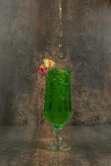 大理石の表面にジューシーなグリーンレモネードとバラのグラス。