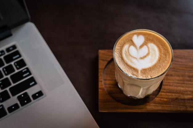 Стакан латте-арт на деревянной тарелке с портативным компьютером и темным фоном
