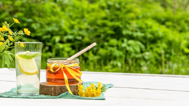 自然界のレモネードと蜂蜜の瓶のガラス。