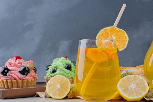 Стакан лимонада и сливочные кексы на столе.