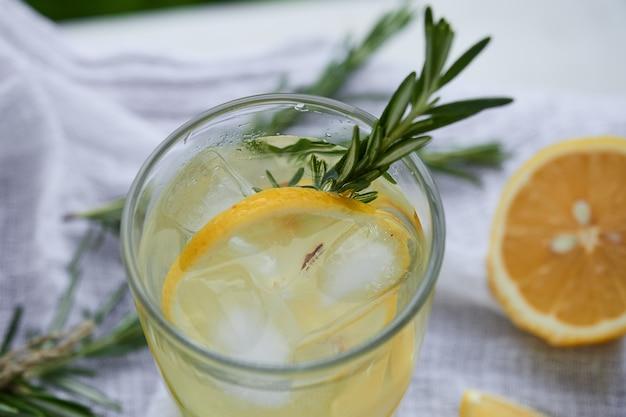 白いナプキンの上面にレモンとローズマリーのスライスとレモネードのガラス