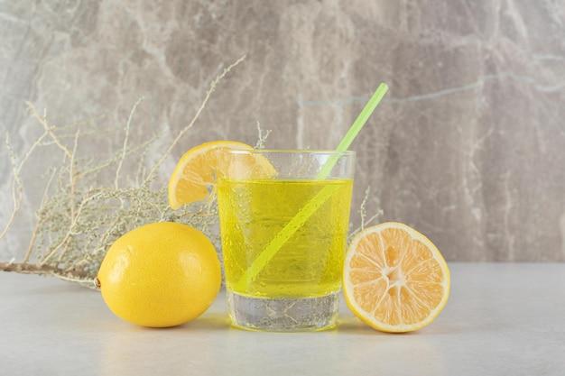 Стакан лимонада с лимоном и соломой на мраморной поверхности