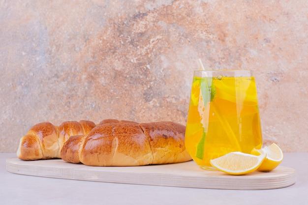白い大皿に甘いパンとレモネードのグラス。