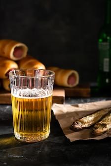 黒いテーブルの上に軽いビールと2つの干物のグラス