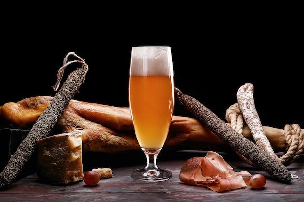 軽いビールの泡、脚、パルマハム、高価な種類のソーセージ、カビの生えたチーズのグラス。黒の背景に。ロゴの場所。