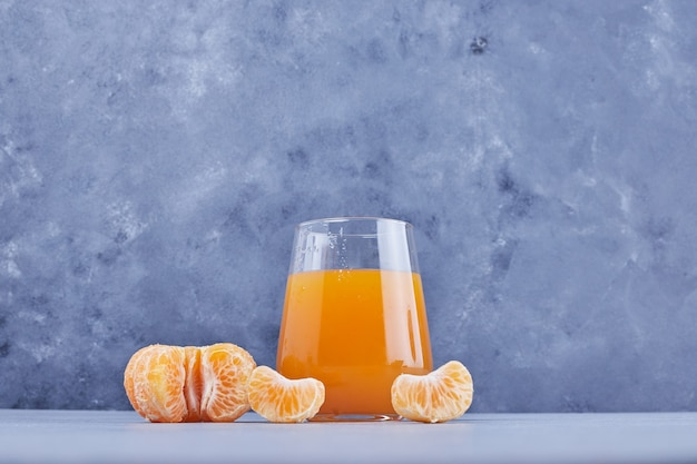 果物が周りにあるマンダリンジュースのグラス。