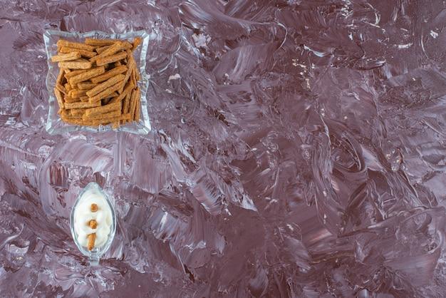 大理石のテーブルの上にあるガラスのボウルにマヨネーズとカリカリのパン粉を入れたグラス。