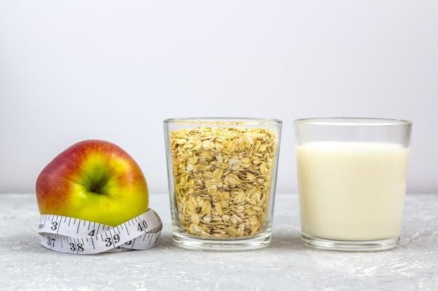 Стакан молока и стакан овсяных хлопьев (овсяные хлопья). яблоко с рулеткой.