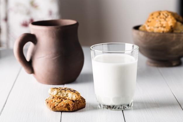 Стакан молока и печенья на деревянном столе на светлом фоне.