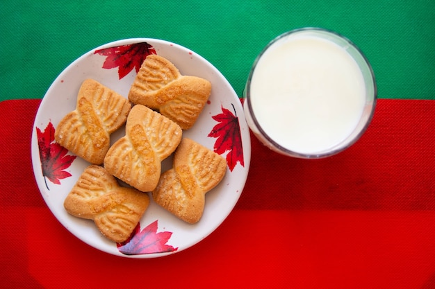 赤と緑の背景を持つプレート上のミルクとクッキーまたはショートケーキビスケットのガラス。全国クッキーデーの背景。サンタさんのクリスマスの朝食。アメリカンブレックファースト