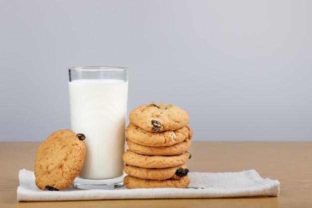 Стакан молока и печенье с изюмом на столе