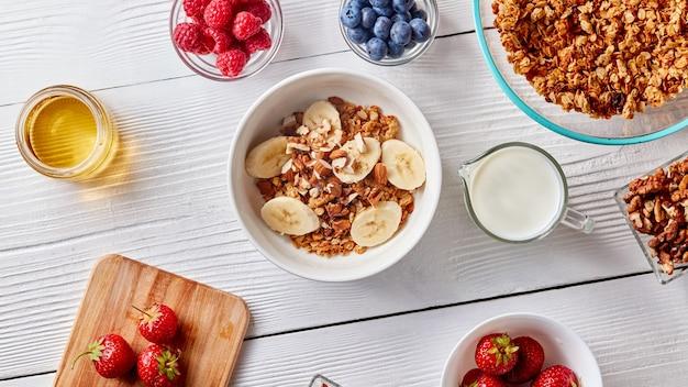 Стакан молока, разные сочные ягоды, мед и тарелка с мюсли и кусочками банана.