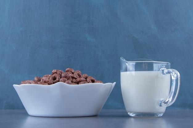 大理石の背景に、ボウルのトウモロコシのリングの横にあるミルクのガラス。