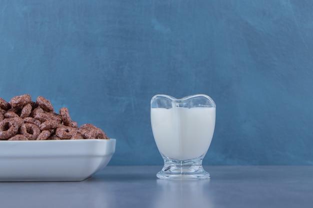 大理石のテーブルの上にあるガラスのボウルのトウモロコシの指輪の横にあるミルクのグラス。 無料写真