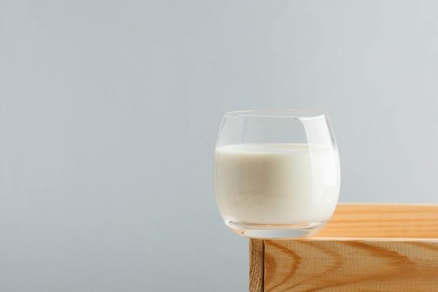 Стакан молока на светлом фоне на деревянном ящике концепция фермы молочных продуктов использование ...