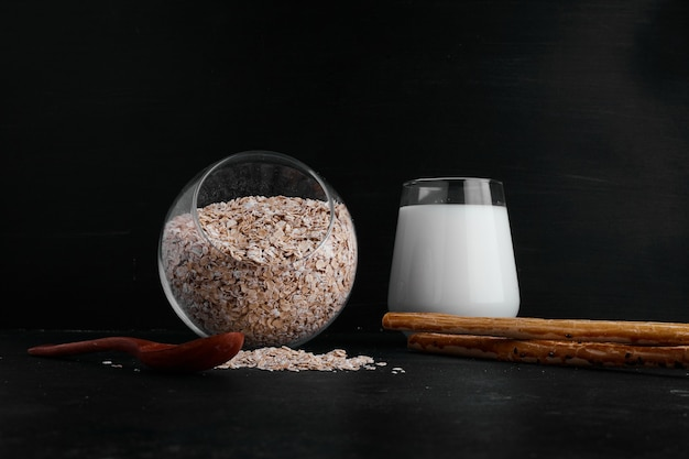 Стакан молока подается с чашкой зерна на черной поверхности.