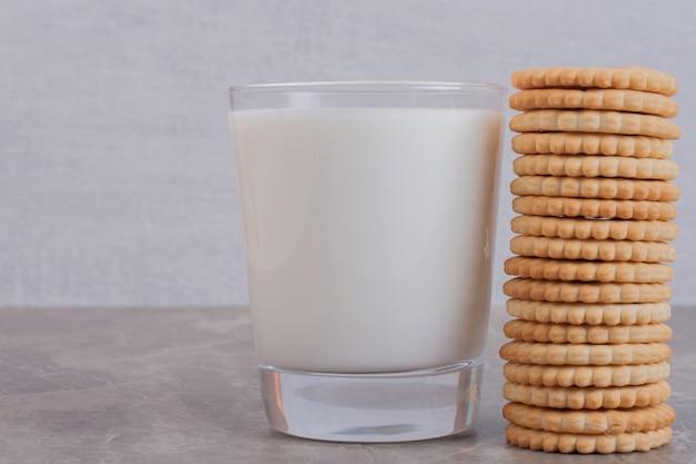白いテーブルの上のクッキーとミルクのガラス