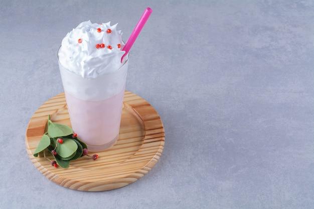 Стакан молочного коктейля со сливками на деревянной тарелке, на мраморном фоне.