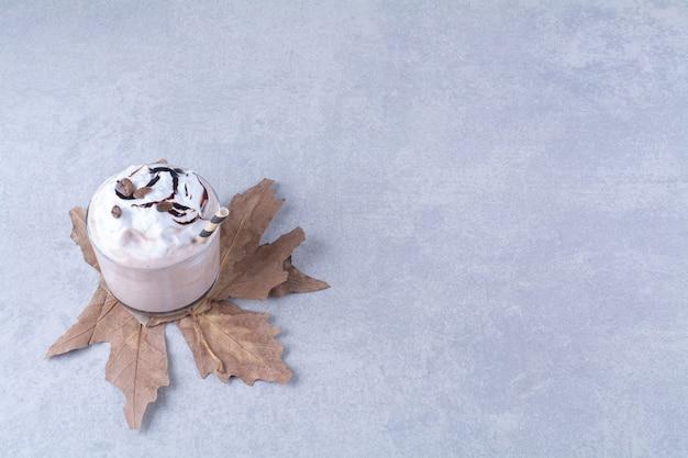 대리석 테이블에 짚이 달린 밀크셰이크 한 잔.
