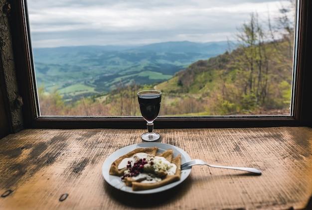 Бокал глинтвейна и сырники с окном с видом на горы и долины