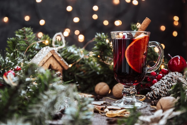 Бокал глинтвейна в новогодней обстановке, горячее вино.