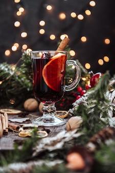 Бокал глинтвейна в новогодней обстановке, горячее вино. вертикальное фото.