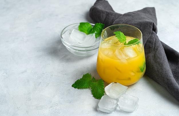 린넨 냅킨이있는 밝은 회색 책상에 민트와 얼음 조각이있는 오렌지 칵테일 한잔. 상쾌한 음료의 개념.