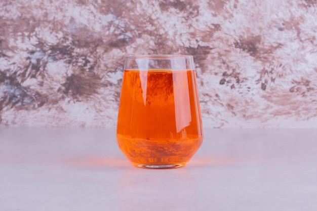 大理石の上のオレンジ色の飲み物のガラス。