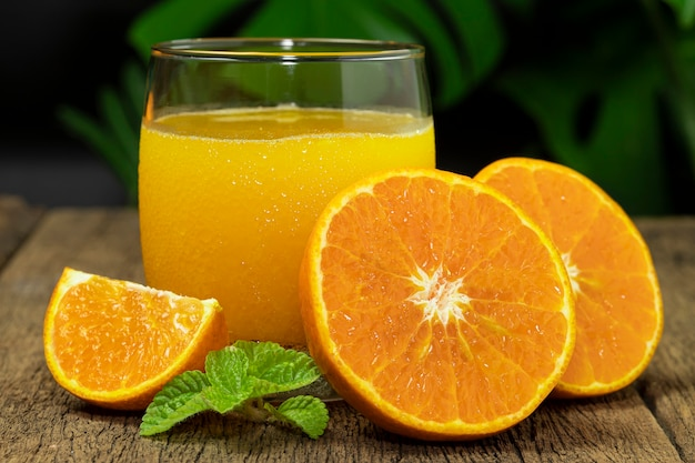 オレンジジュースとオレンジフルーツのグラスを木製のテーブルで半分にカットしました。