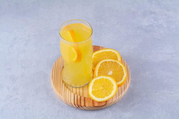대리석 테이블에 나무 접시에 오렌지 슬라이스 옆에 오렌지 주스 한 잔.