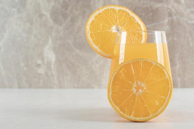 灰色のテーブルにオレンジジュースのガラス