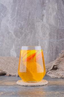 大理石の上のオレンジジュースのガラス。
