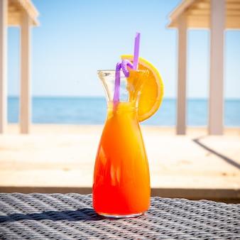 ビーチで地面にオレンジジュースのガラス。側面図。