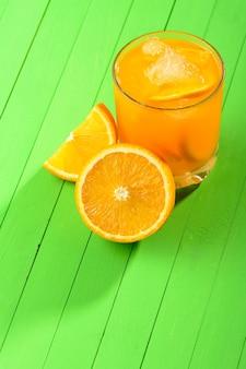 緑の木製テーブルに氷とオレンジジュースのガラス