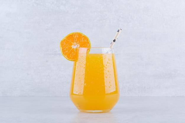 돌에 짚으로 오렌지 주스 한 잔