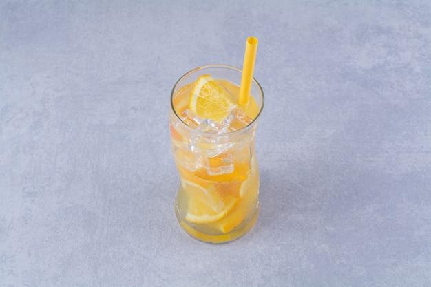 大理石の背景に、ジューシーなオレンジ色のグラス。