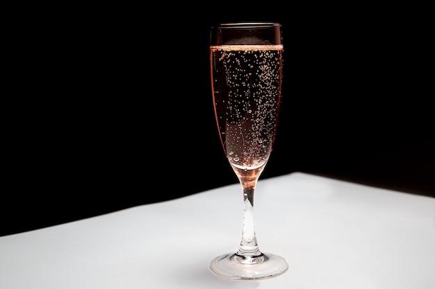 Бокал розового шампанского на столе