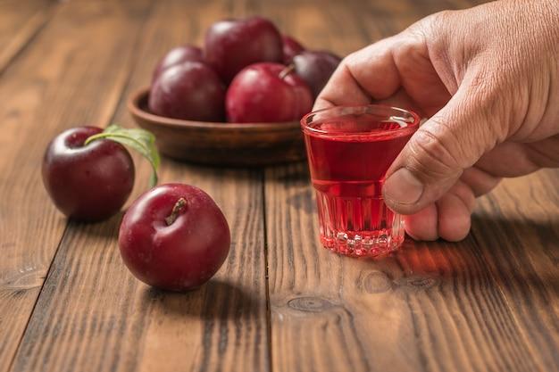 収穫梅の表面に男の手に梅アルコールのガラス
