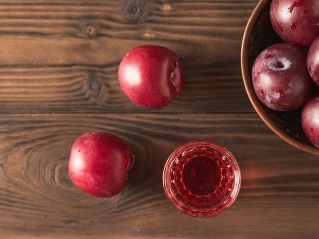 梅酒のグラスとテーブルの上の梅のボウル