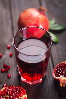 나무 테이블에 신선한 석류 과일과 함께 석류 주스 한 잔. 비타민과 미네랄을 함유하고 있어 헤모글로빈 증가에 도움