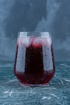 파란색 배경에 가공 된 주스 한 잔. 고품질 사진