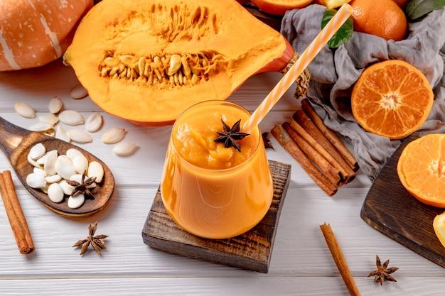 Стакан смузи из тыквы и апельсина на столе. фото высокого качества