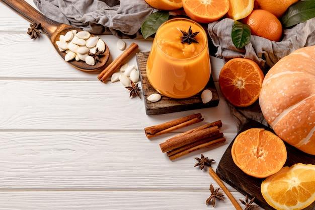 Стакан смузи из тыквы и апельсина со специями на столе. свободное место для вашего текста. фото высокого качества