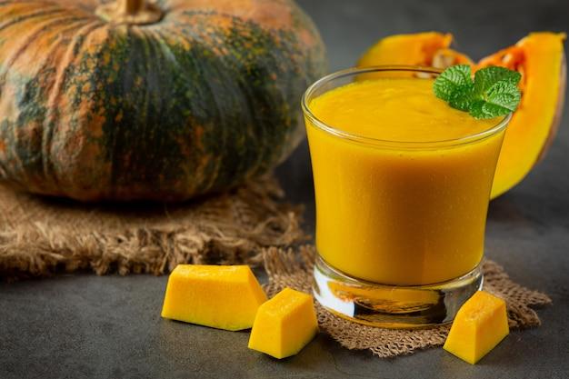 かぼちゃジュースと刻んだ生かぼちゃを暗い床に置きます