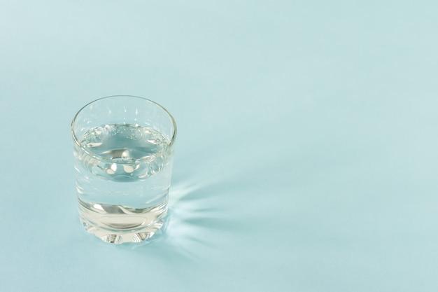 Стакан чистой воды на синем фоне. скопируйте место для текста. концепция здорового образа жизни и диеты.