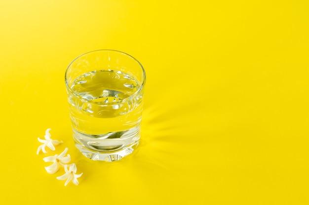 Стакан чистой воды на желтом фоне. скопируйте место для текста. концепция здорового образа жизни и диеты.