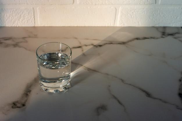 Стакан очищенной пресной питьевой воды на мраморном столе. скопируйте место для текста.