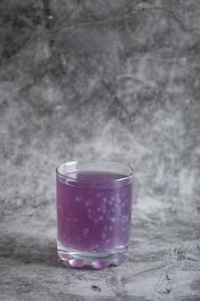 Стакан фиолетового сока черники на сером.